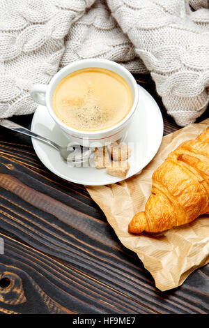 cup of coffe and croissant on wooden background - Stock Photo