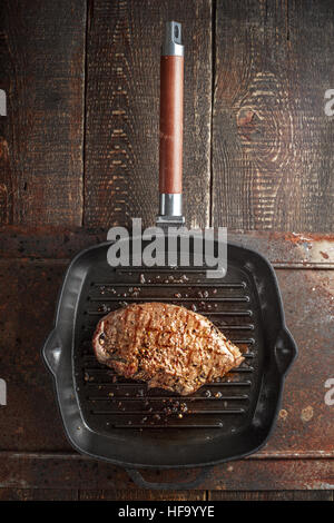 Roast beef steak in spices on pan grill on the table vertical - Stock Photo