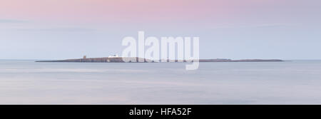 Farne Islands at sunset off the Northumberland coast in the winter time with dusky pink and blue pastel colours, - Stock Photo