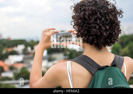 Girl with beautiful short curly hair taking pictures of a city. Using green backpack. - Stock Photo