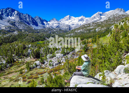Hiker at overlook by the Mono Pass Trail enjoys view of Little Lakes Valley in Rock Creek Canyon - Stock Photo