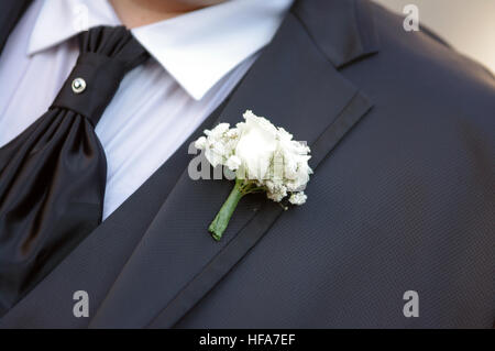 pin with decorative white flowers pinned on the groom's jacket - Stock Photo