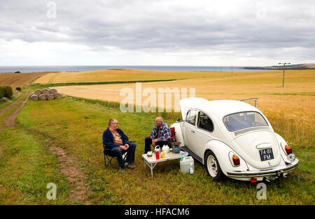 Two Dutch tourists have a picnic beside their VW beetle in a field near St Abbs, Berwickshire, Scottish Borders, - Stock Photo