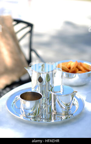 Luxury silver coffee pot on a linen covered table outside in summer. - Stock Photo