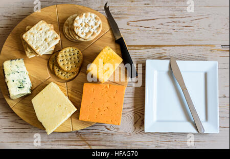 Selection of cheeses on a round cheese board, sitting on an old table. - Stock Photo
