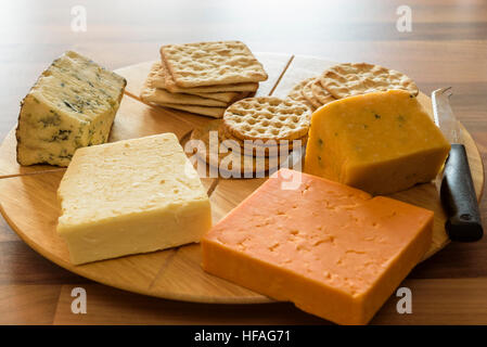 Assortment  of cheeses on a round wooden cheese board. - Stock Photo