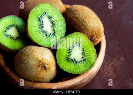 Kiwi fruit in wooden bowl close up - Stock Photo