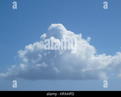A White fluffy cloud in a sunny blue sky - Stock Photo