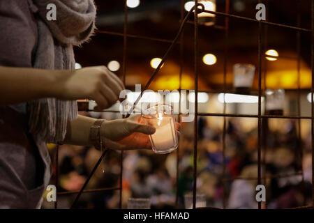 Riga, Latvia. 28th Dec, 2016. A volunteer lights a candle on the altar ahead of the evening prayer. 15,000 pilgrims - Stock Photo