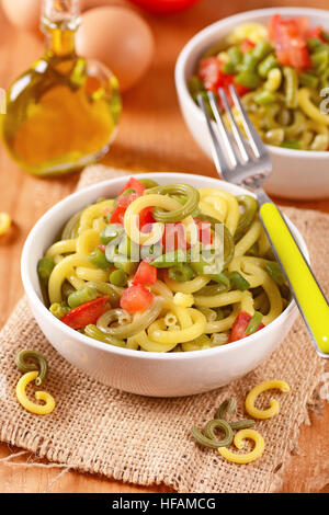 egg pasta two color with green beans and tomato - Stock Photo