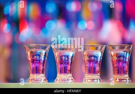 Burning drinks in shot glasses on a bar counter - Stock Photo