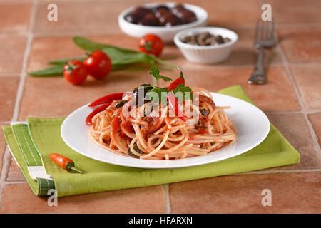 Spaghetti puttanesca - Traditional Italian recipe with anchovies, capers, tomato and chilli - Stock Photo