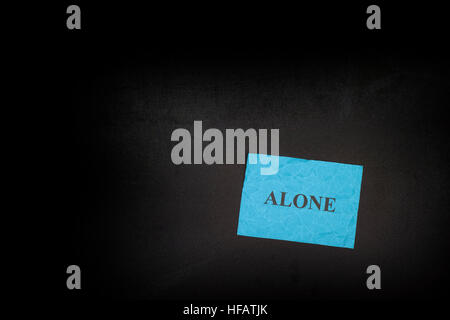 Blue crumpled paper with word Alone on a blackboard. Close up. - Stock Photo