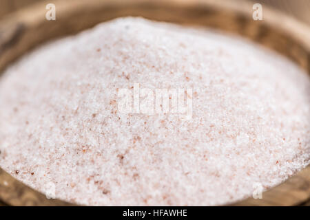 Pink Himalayan Salt on rustic wooden background (close-up shot) - Stock Photo