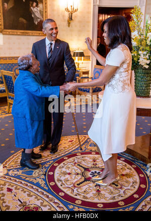 President Barack Obama watches First Lady Michelle Obama dance with 106-Year-Old Virginia McLaurin in the Blue Room - Stock Photo