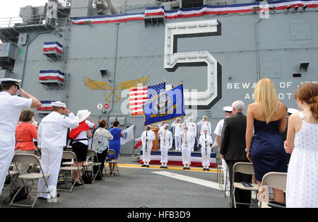 The honor guard parades the colors during a change of command ceremony aboard amphibious assault ship USS Peleliu - Stock Photo