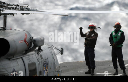 A plane captain signals a MH-60R Seahawk helicopter assigned to Helicopter Maritime Strike Squadron (HSM) 77 as - Stock Photo