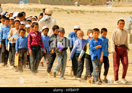 Children from the Homaro Faroq Village near Camp Marmal in Regional Command North, are walking towards the building - Stock Photo