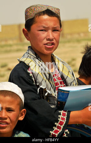 A young Afghan boy from the Homaro Faroq Village near Camp Marmal, Regional Command North, stands with his schoolmates - Stock Photo