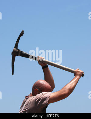Navy Petty Officer 2nd Class William Hunt swings a pickaxe to pry large rocks out of the ground as he prepares the - Stock Photo