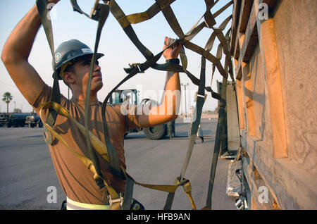Petty Officer James Grace tightens a net to secure tent boxes during Naval Mobile Construction Battalion 3's embark - Stock Photo