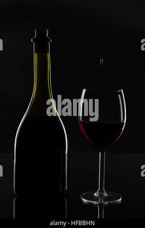 The bottle of wine and a drop in the glass. - Stock Photo