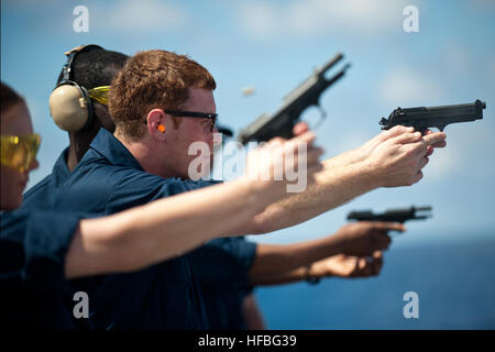 SOUTH CHINA SEA (July 7, 2012) Operations Specialist 2nd Class Adam Darisse takes aim with an 9 mm pistol during - Stock Photo