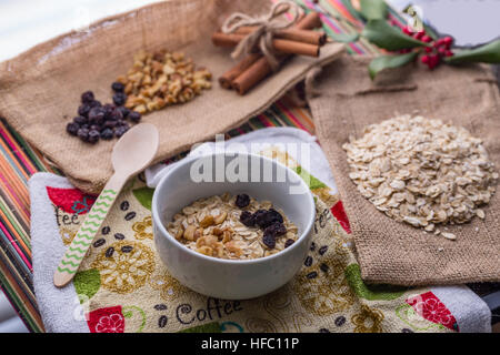 Oatmeal breakfast with walnut, raisin, and cinnamon in milk. - Stock Photo
