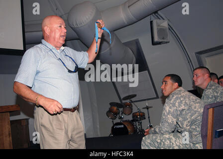 GUANTANAMO BAY, Cuba – Retired Army Sgt. Maj. Gary Littrell, a Medal of Honor recipient, removes his medal from his neck to pass around to service members at Joint Task Force Guantanamo, July 29, 2009. Littrell travels the country telling his stories and the importance of patriotism, leadership, democracy and the history of the Medal of Honor. JTF Guantanamo conducts safe, humane, legal and transparent care and custody of detainees, including those convicted by military commission and those ordered released by a court. The JTF conducts intelligence collection, analysis and dissemination for th