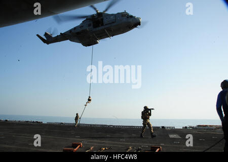 Italian marines conduct a fast-rope exercise from an Italian navy EH-101 Merlin helicopter onto the flight deck - Stock Photo