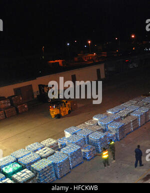 Sailors assigned to Naval Cargo Handling Battalion 1, based in Williamsburg, Va., stage pallets of water at U.S. - Stock Photo