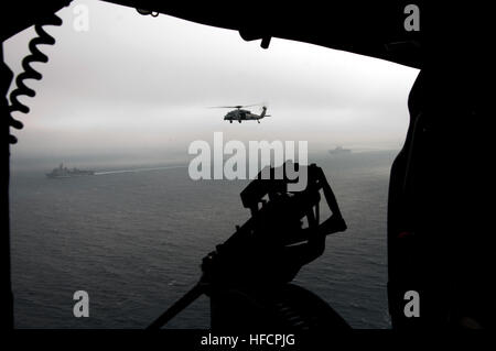 A U.S. Navy SH-60 Seahawk helicopter flies above the amphibious dock landing ship USS Rushmore (LSD 47), left, and - Stock Photo