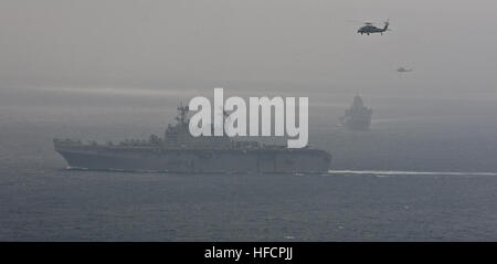 A U.S. Navy SH-60 Seahawk Helicopter, top left, and a U.S. Marine Corps UH-1Y Viper helicopter fly over the the - Stock Photo