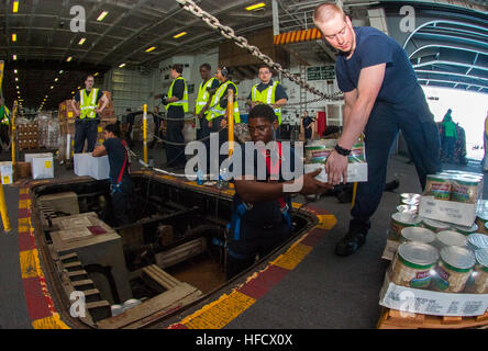150714-N-YD641-059 TIMOR SEA (July 14, 2015) Sailors move cargo in the hangar bay of the Nimitz-class aircraft carrier - Stock Photo