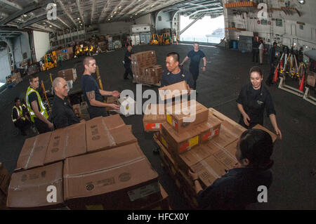 150714-N-YD641-086 TIMOR SEA (July 14, 2015) Sailors move cargo in the hangar bay of the Nimitz-class aircraft carrier - Stock Photo