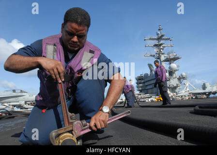Aviation boatswain's mate (fuels) Petty Officer 1st Class Antonio Osorio tightens a hydrostatic test cap onto the - Stock Photo