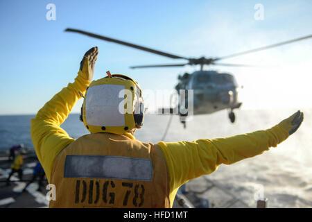 MEDITERRANEAN SEA (Dec. 2, 2016) Petty Officer 2nd Class Brantley Harper signals the pilot of an MH-60 Seahawk, - Stock Photo
