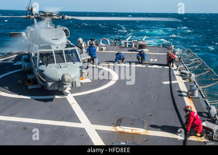 150713-N-XM324-041 TIMOR SEA (JULY 13, 2015) Sailors refuel an MH-60R Seahawk helicopter, assigned to the 'Saberhawks' - Stock Photo