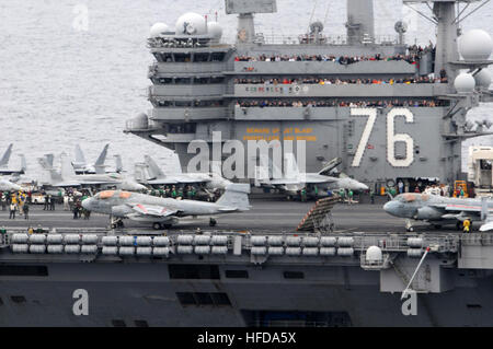 Tigers line all available spaces at the top of the island to watch flight operations on board the Nimitz-class aircraft - Stock Photo