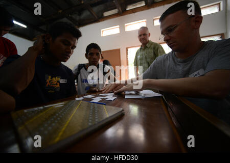 Fuca, a Timorese college student attending the Universidade Nacional Timor Lorosa'e, completes an English exercise - Stock Photo