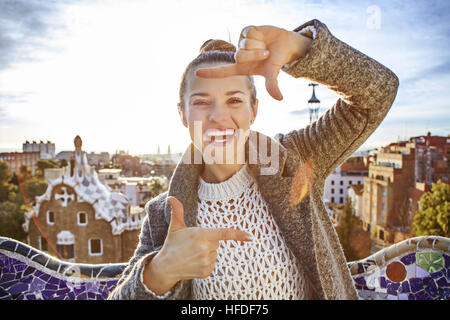 Barcelona signature style. smiling elegant traveller woman in coat in Barcelona, Spain framing with hands - Stock Photo