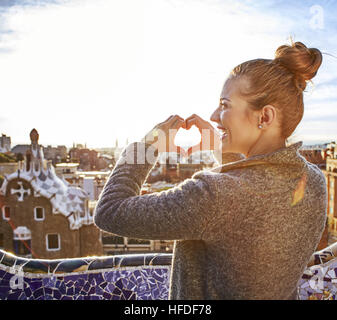 Barcelona signature style. Seen from behind young tourist woman in coat in Barcelona, Spain showing heart shaped - Stock Photo