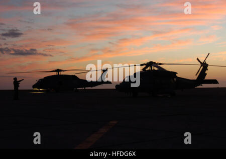 Aircrew directs Navy helicopters at U.S. Naval Station Guantanamo Bay airfield as the sunsets, Jan. 19. The aircraft - Stock Photo
