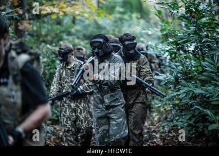 Groups of people dressed up in combat camouflage  uniforms and carrying paint-ball guns hunting zombies in the woods - Stock Photo