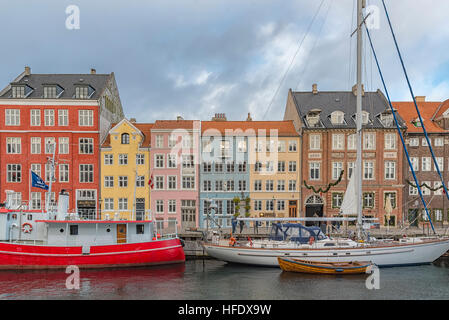 Nyhavn district is one of the most famous landmarks in Copenhagen, Denmark and always packed with tourists. - Stock Photo