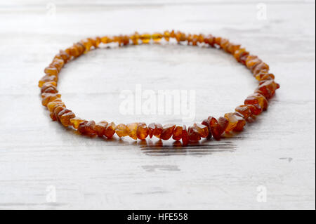 Bright orange amber necklace of raw beads     string on an old gray wooden background - Stock Photo