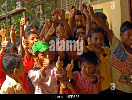 050117-N-9951E-190 Region of Glebruk, Sumatra, Indonesia (Jan. 17, 2005) Ð Indonesian children give a thumbs-up - Stock Photo