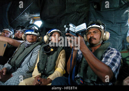 050123-N-9885M-489 Sumatra, Indonesia- Indonesians and relief workers travel aboard an MH-53E helicopter as they - Stock Photo