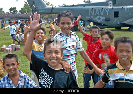 050123-N-9885M-136 Lamno, Indonesia- Indonesian kids gather around a MH-53E Sea Dragon helicopter as crewmembers - Stock Photo