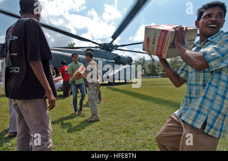 050123-N-9885M-250 Lamno, Indonesia- Indonesians carry boxes of noodles from a MH-53E Sea Dragon helicopter, as - Stock Photo